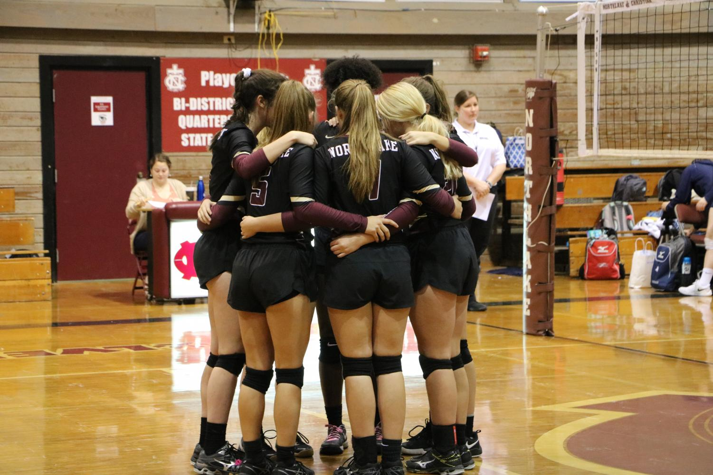 Varsity girls huddle together during game at Northlake, showing unity