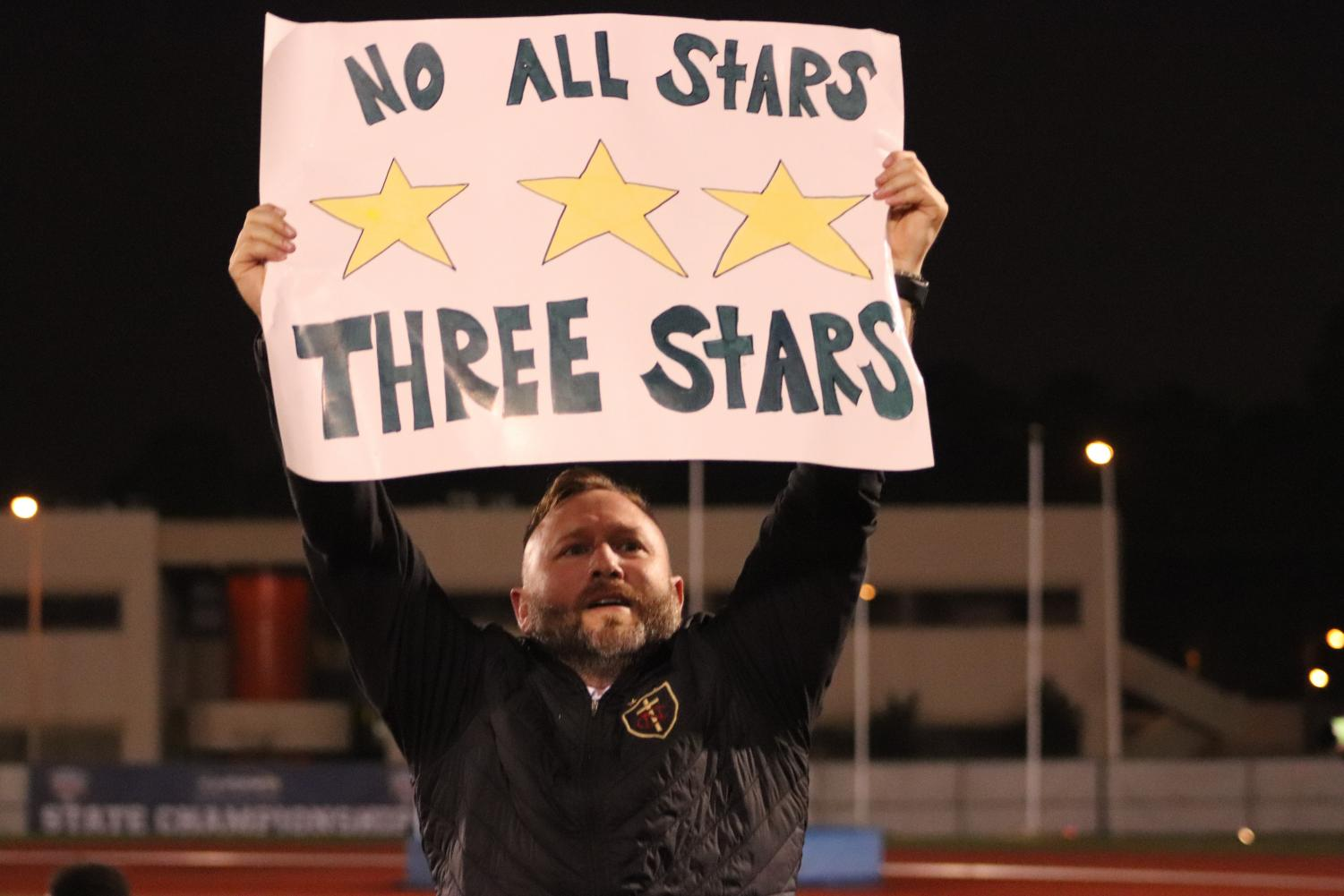 Head Coach Nick Chetta holds signs that says,