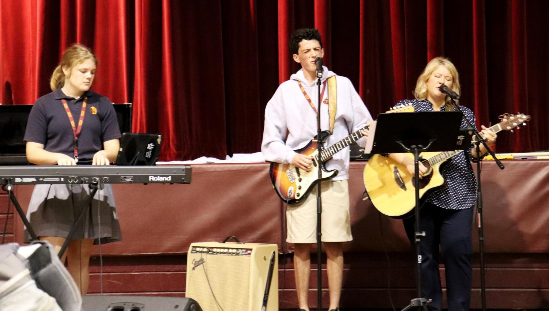 Praise Team member lead worship during Upper School chapel alongside teacher Kate Boudreaux (right).