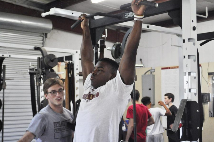 Senior Wesley Brown does pull-ups during Athletic P.E. alongside football teammate Clay Thrasher.