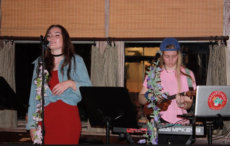 Sophomores Isabel Mathes (left) and Lillian Stegen (right) perform at St. Johns Coffeehouse in Madisonville, La.