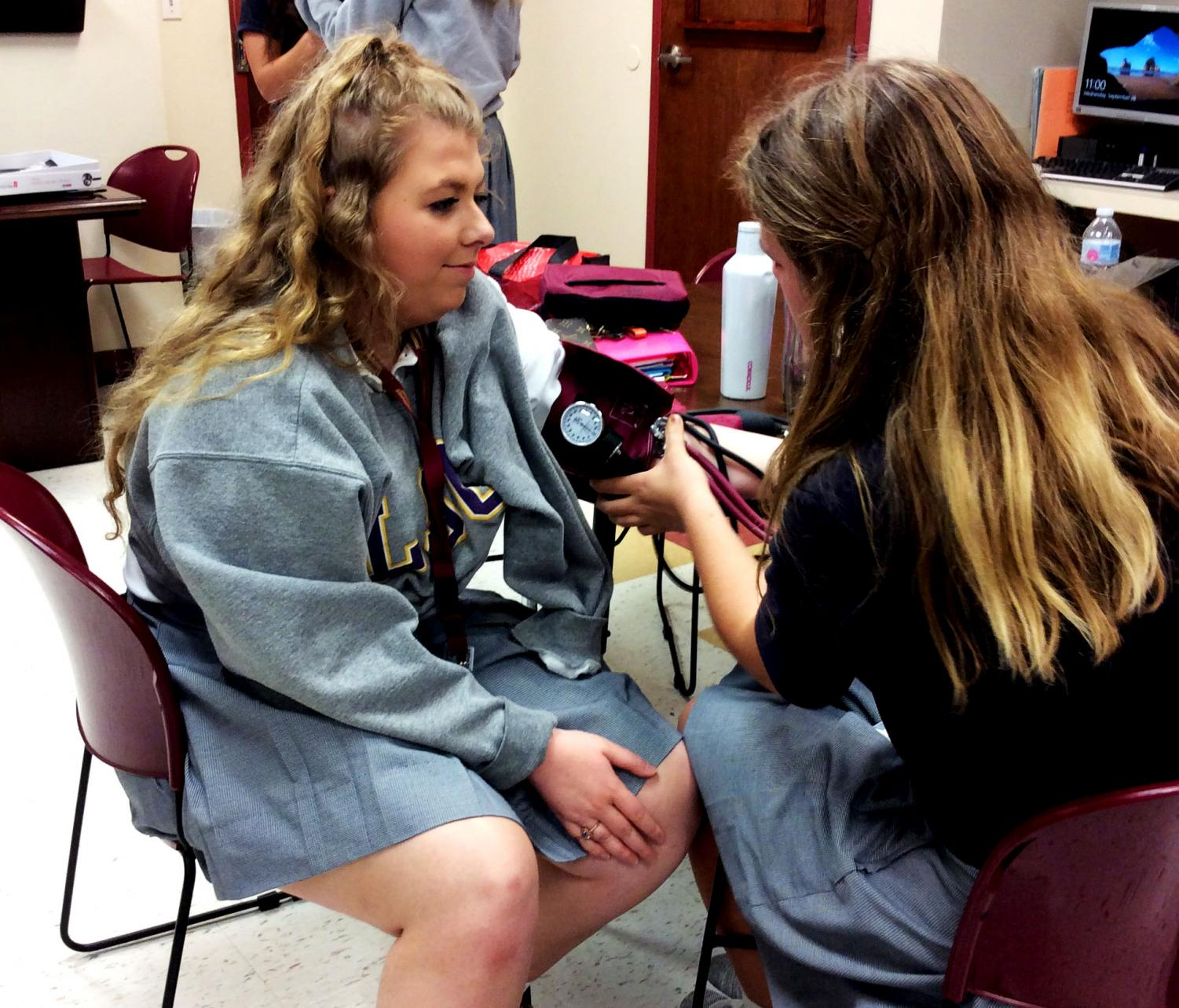 Student Katelyn Simpson practices on Emily Craig during a Certified Nursing Assistant class.