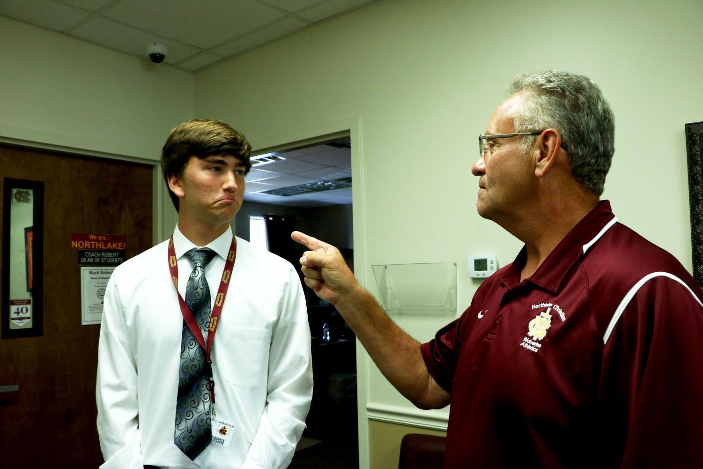 Coach Mark Robert pretends to scold reporter Colton Leggett.