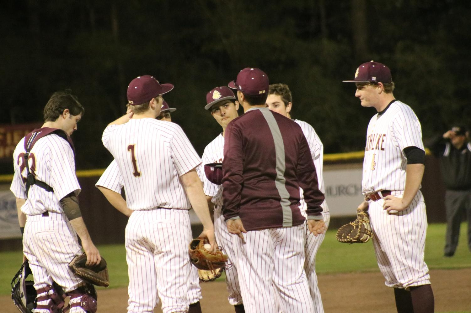 The Wolverine Baseball team gather around the mound mid-game to make adjustments with Coach Cam.