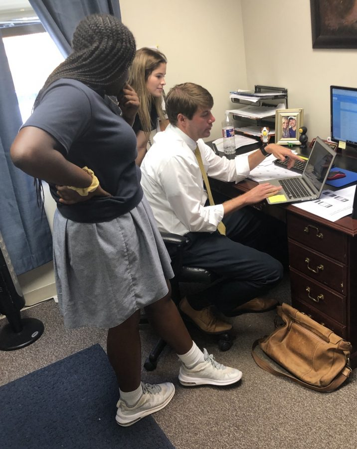 Upper School Academic Dean Matt McCune helps two students in his office.