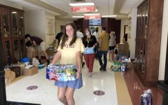 Katelyn James, along with other students and faculty, is pictured here helping carry items to the trailer.